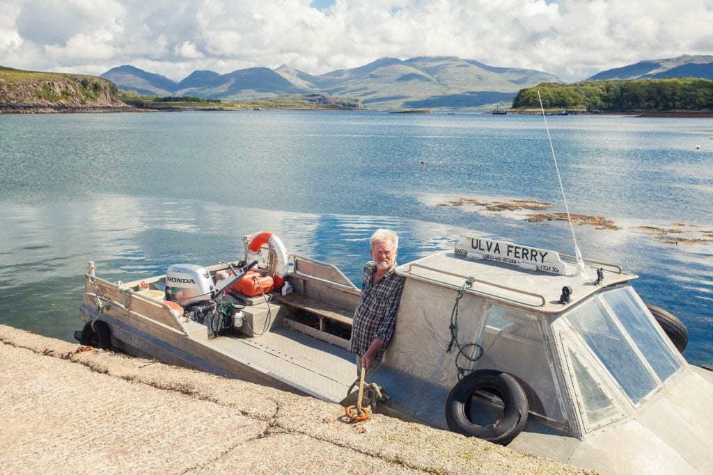 A man standing at the small Ulva passenger ferry on the Isle of Mull.