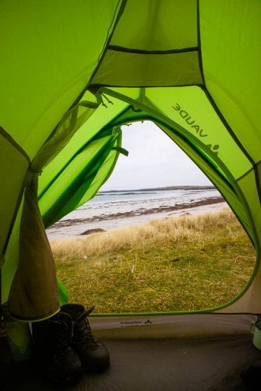 View from a green tent onto a beach.