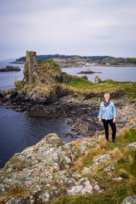 A woman in denim jacket standing by a castle ruin by the sea. Dunyvaig Castle on Islay