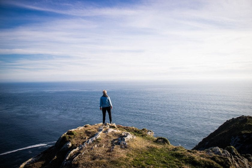 A woman standing on a cliff overlooking the ocean