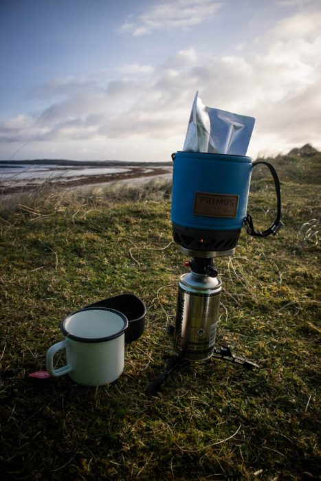 Cooking breakfast on a camping stove by a beach.