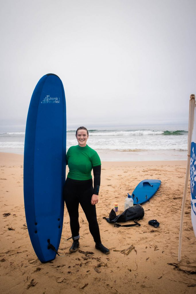 Woman in a wet suit with a surf board at the beach