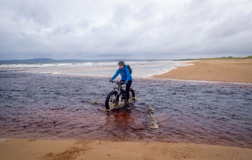 A woman fat biking on the beach
