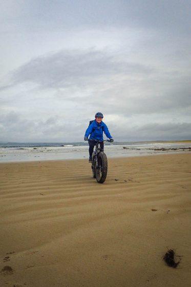 A woman cycling a fat bike on a beach