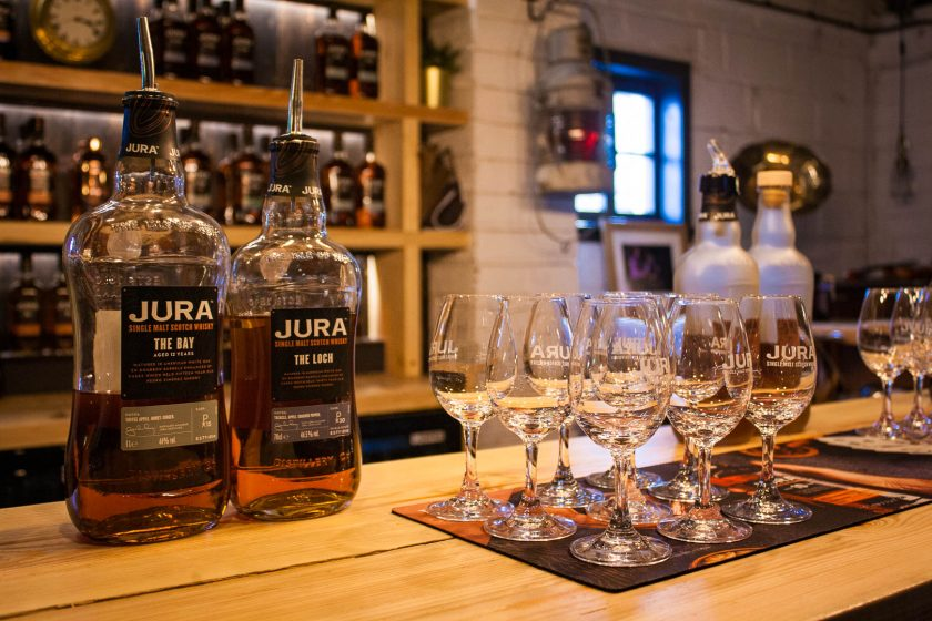 Bottles of Jura whisy and glasses on a bar counter