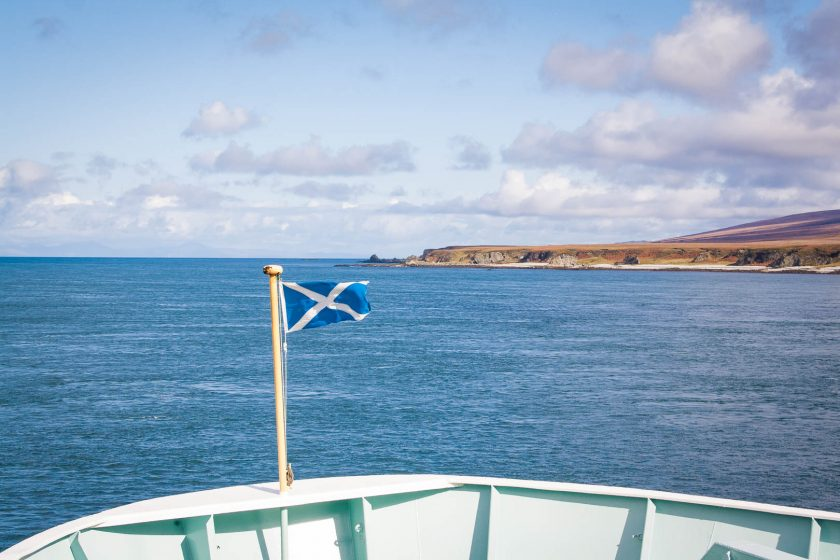 Scotland flag at the front of a ferry with and island in the background.