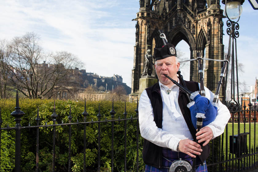 A bagpiper in front of the Scotts Monument in Edinburgh.