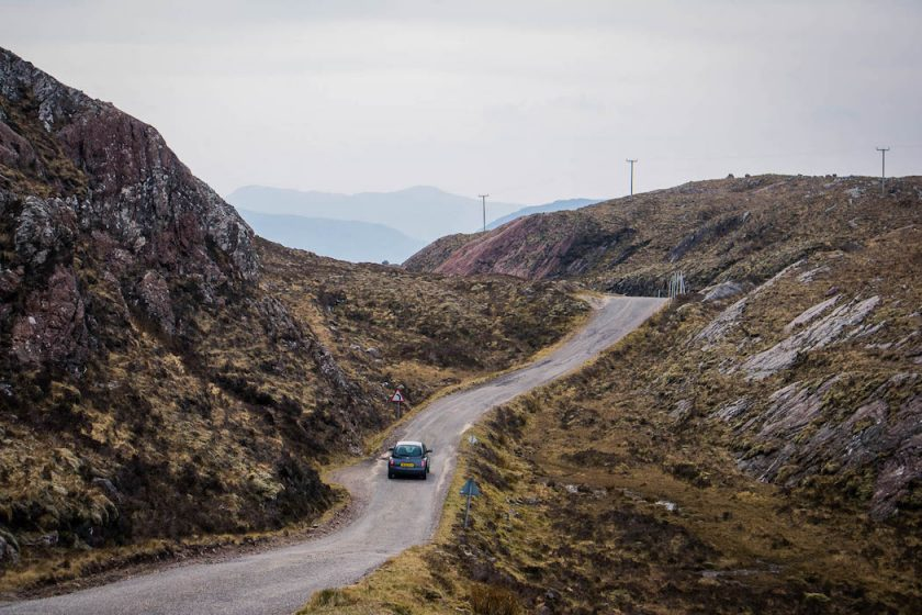 A car on a winding single track road on the NC500 in Scotland