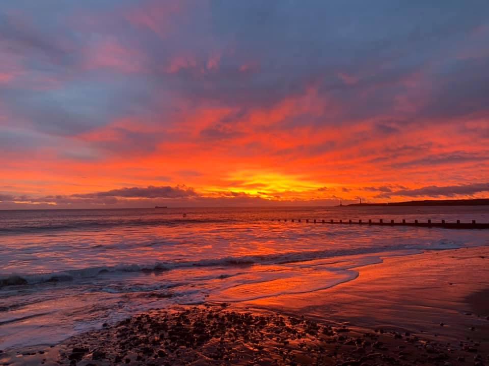 A vivid red sunrise over the ocean at Aberdeen beach