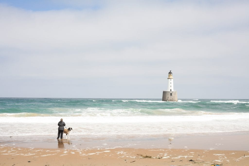 Rattray Head Lighthouse stands tall on a rock in the middle of the ocean. The lighthouse is only accessible during low tide, but during high tide, it's surrounded by the crashing waves of the Atlantic.