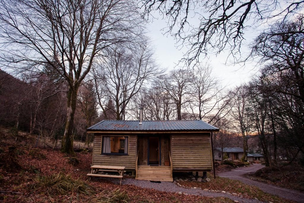 A wooden cabin in the woods in Scotland.