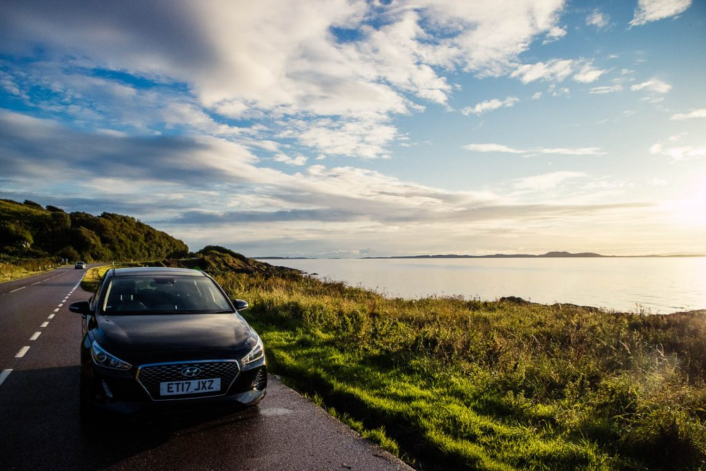 a car on the road by the coast in scotland