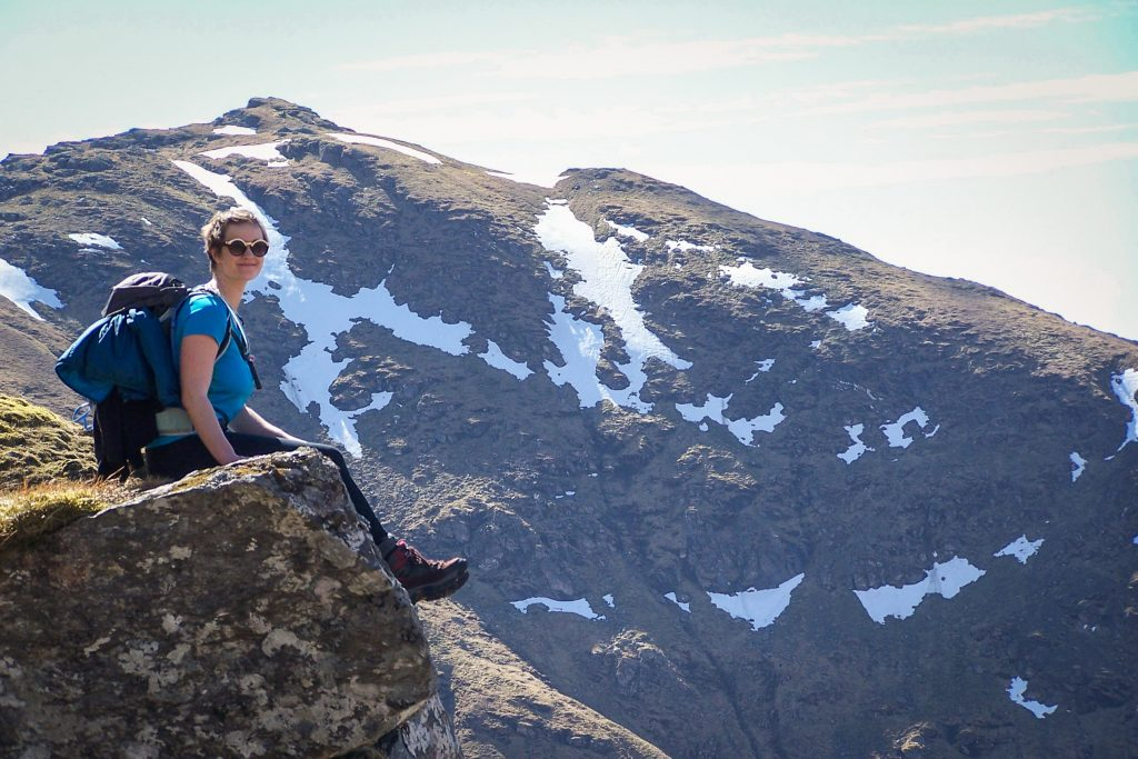 A woman sitting on a rock ledge in the Scottish Highlands.