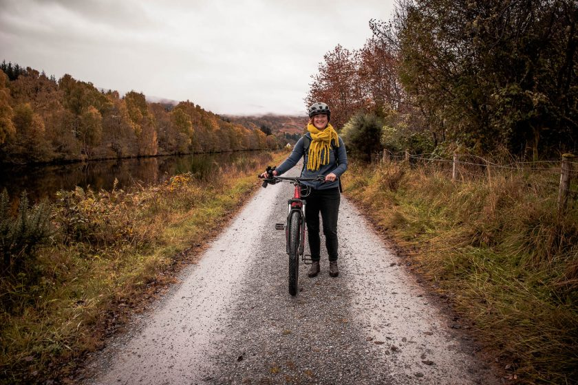 A woman with an ebike next to the Caledonian Canal near Loch Ness in Scotland