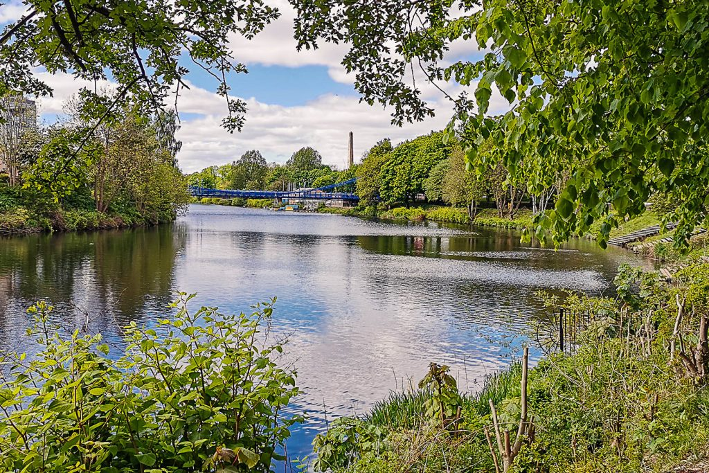 View of the river, blue bridge and stone obelisk on a river walk in Glasgow