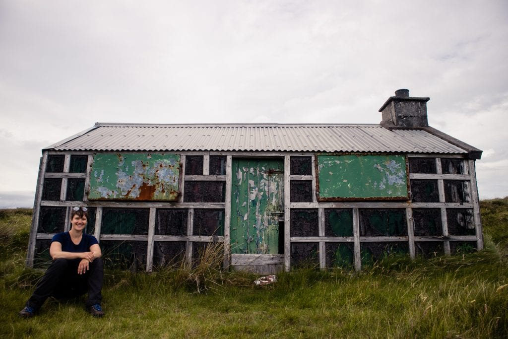 Girl sitting in front of an old shieling in the moor of Lewis