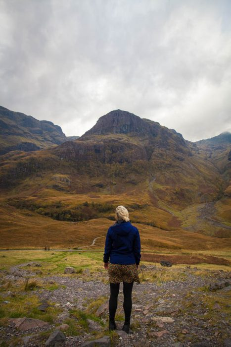 A woman standing in front of mountains in Glencoe.