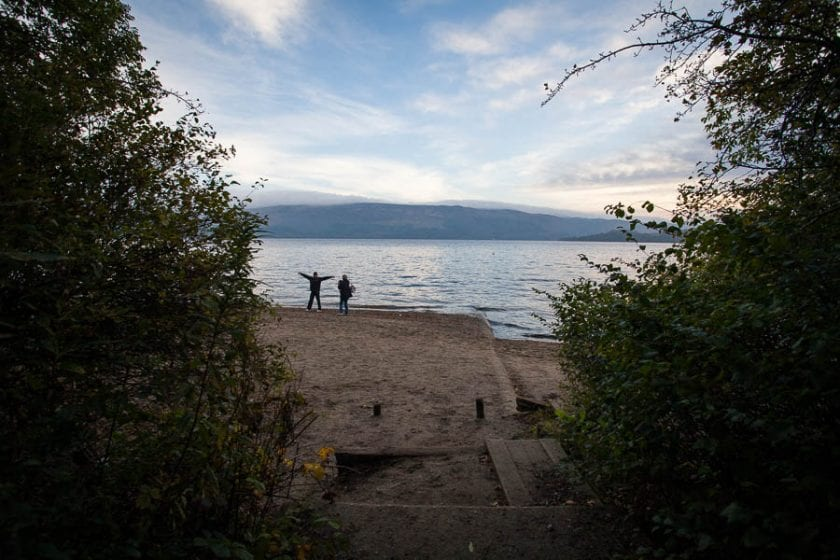 Two people standing by the beach of Loch Lomond.