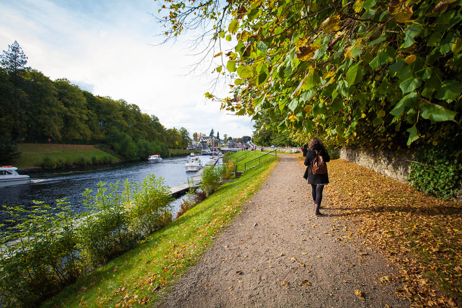 A woman walking along the river in Fort Augustus.