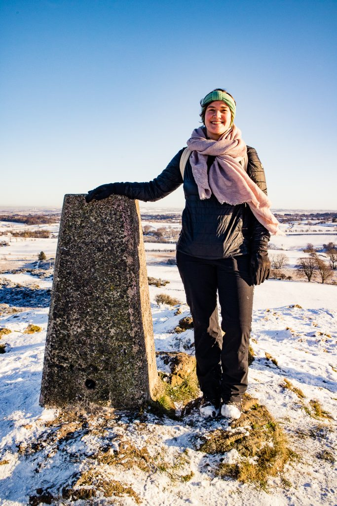 A hiker at the summit trig point of Duncarnock Fort Hike in Glasgow