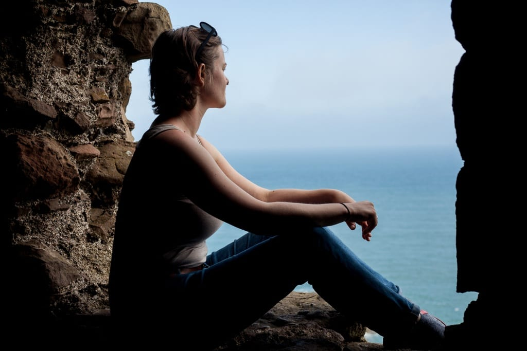 A woman sitting in a stone window at Dunnottar Castle in Scotland