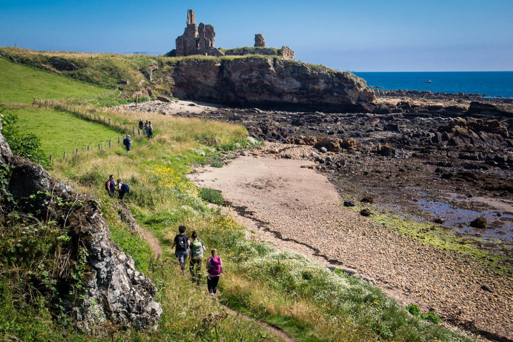 Women hiking on a path towards the ruins of Newark Castle in Scotland