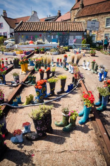 A quirky garden made up of rubber boots with plants inside them.