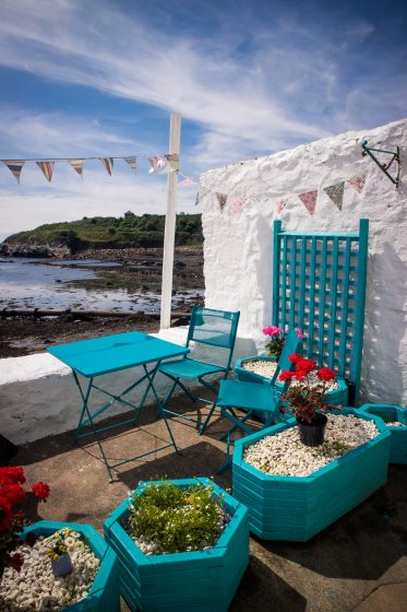 A seaside terrace with white-washed walls and bright blue cafe furniture. There is also colourful bunting.