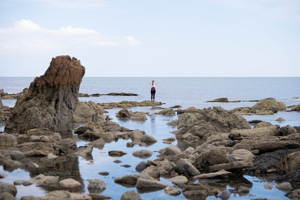 A woman standing on rocks by the sea on the FIfe Coastal Path in Scotland.
