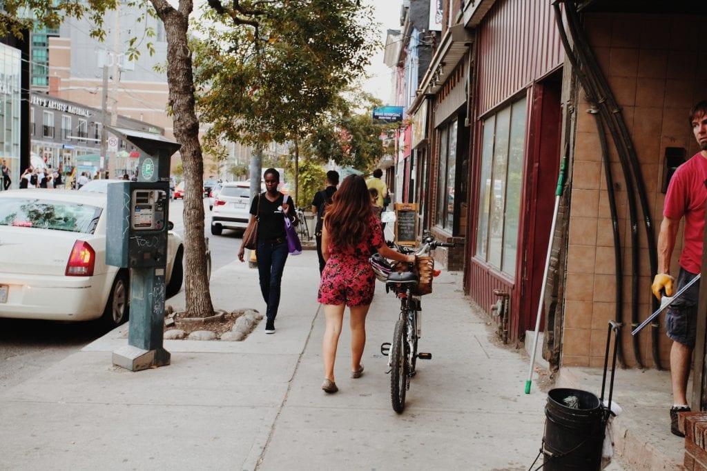Girl walking her bike in West Queen West in Toronto - 30 things to do in Toronto - Photo by Kathi Kamleitner