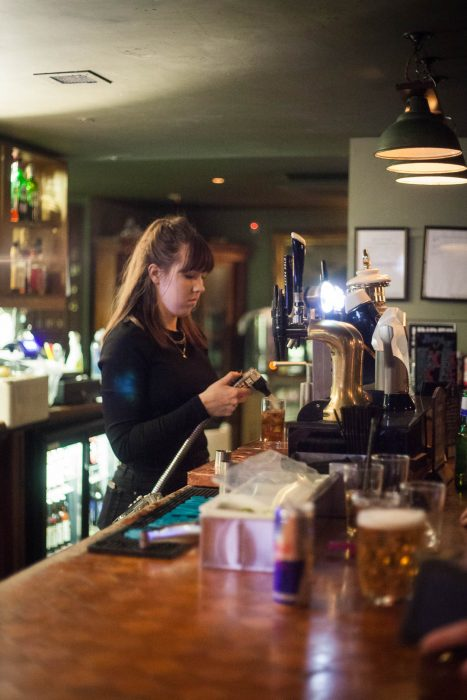 A barmaid pouring drinks at the Butterfly & the Pig pub in Glasgow.