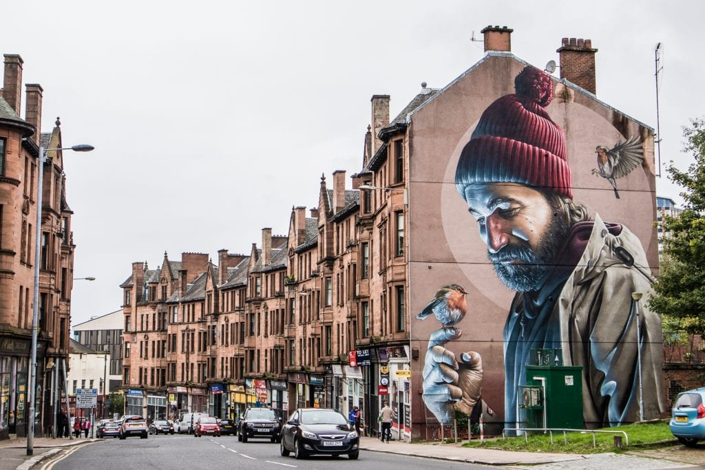 Mural of St Mungo in Glasgow. | Planning a trip to Scotland is a daunting task - especially when it's your first time. You could begin by locking down dates or mapping out a route, but this list of things to taste, feel, do & see allows you plan a trip around once-in-a-lifetime experiences you must have when traveling to Scotland for the first time!