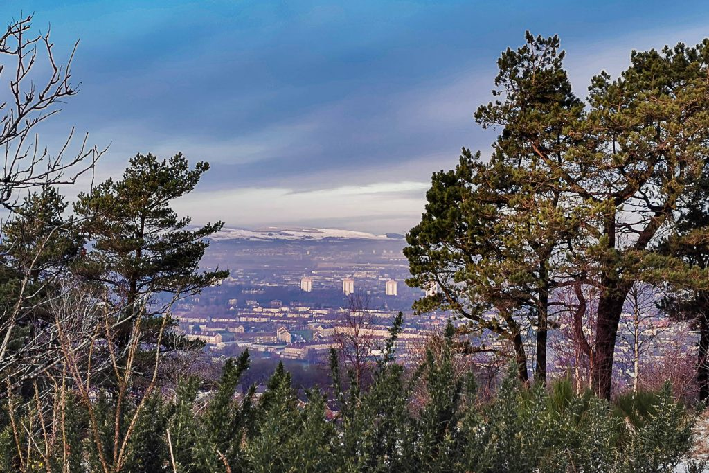 View of Paisley and mountains through trees from Gleniffer Braes walk in Glasgow