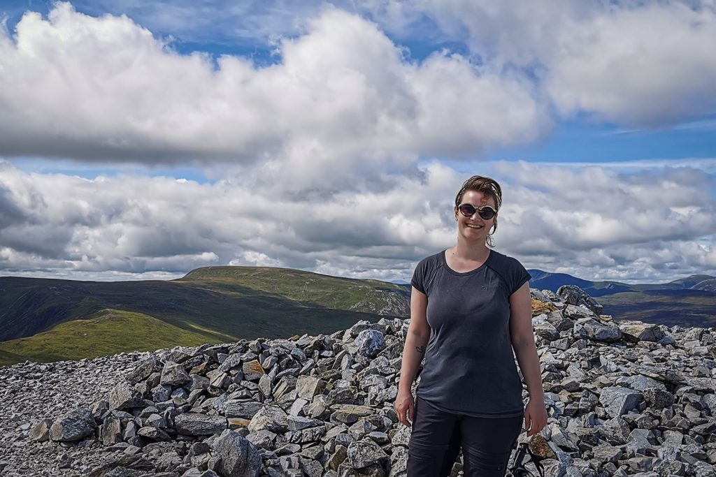 A woman standing at the rocky summit of a Scottish munro in the Cairngorms.