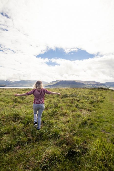 A woman running through the meadow on Ulva.
