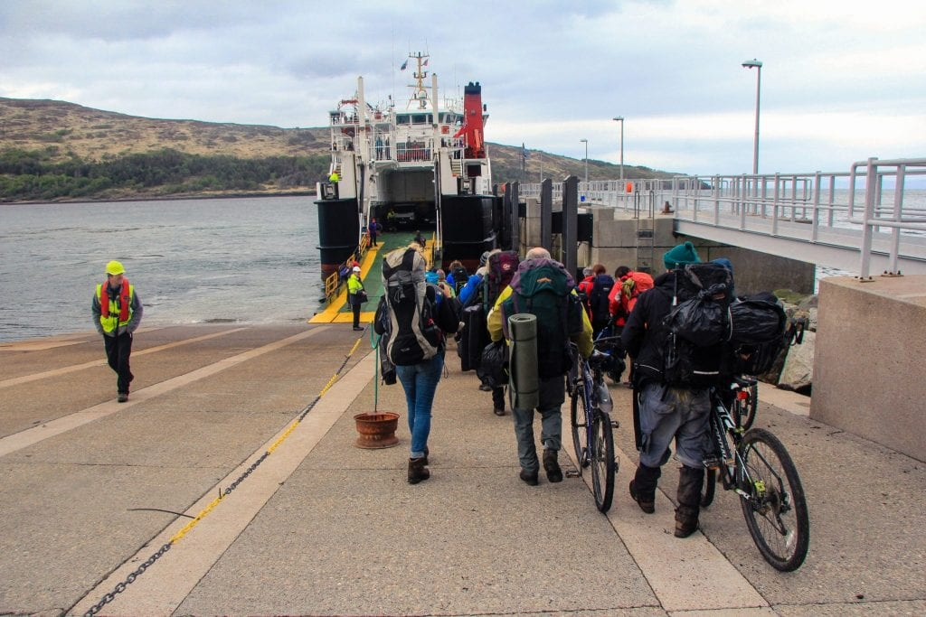 The photo shoes a group of people with camping and cycling equipment boarding the ferry from the Isle of Rum to Mallaig in Scotland.