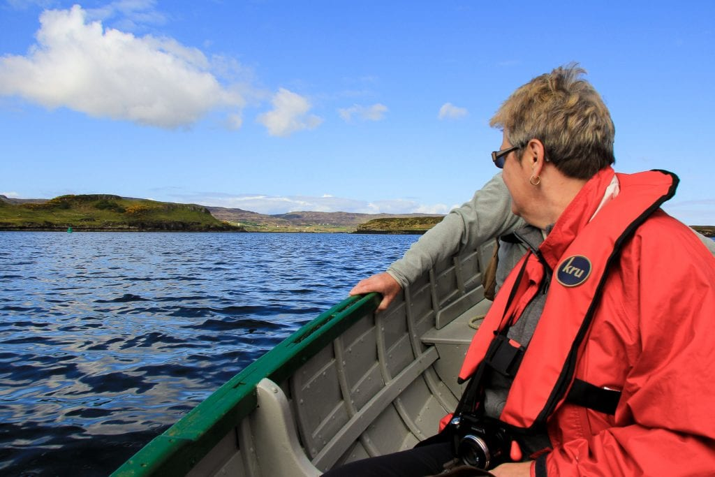 A woman on a boat watching wildlife in Scotland.