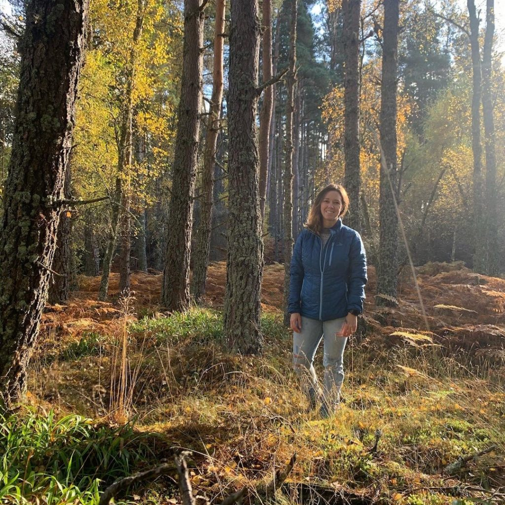 A woman standing in the forest in autumn