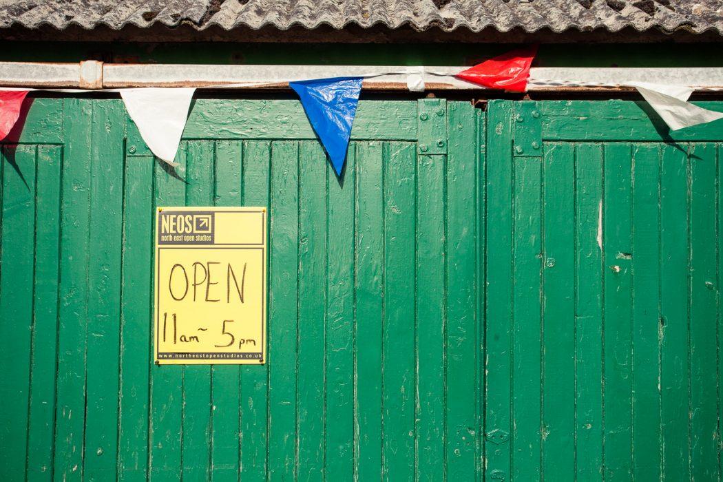 Yellow North East Open Studios sign on a green door.