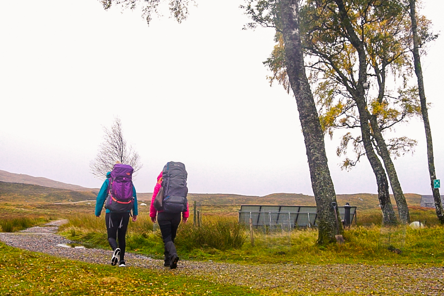 Two women carrying backpacks outside the Loch Ossian Youth Hostel.
