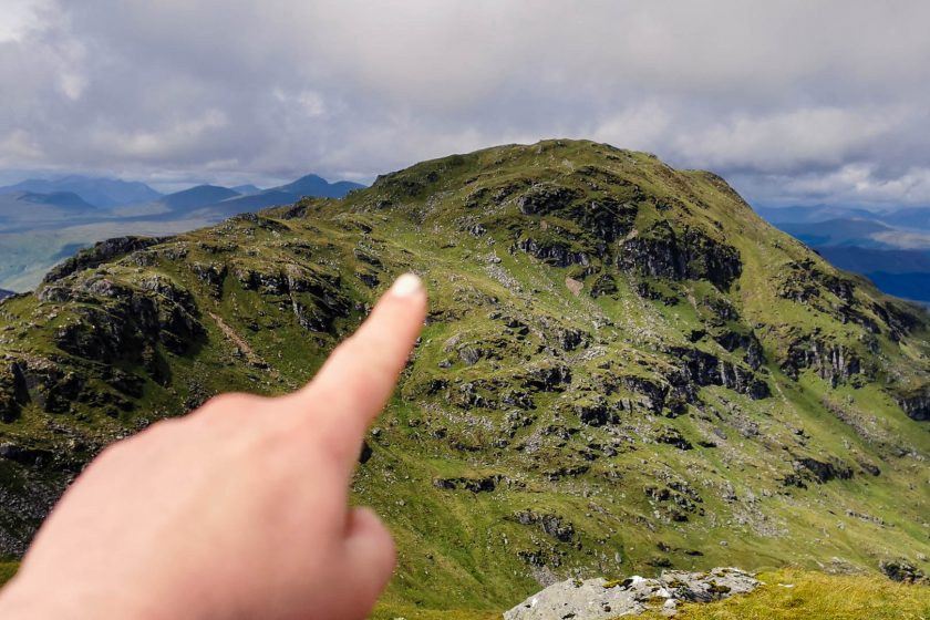 A hand pointing at the peak of An Caisteal in the Scottish Highlands