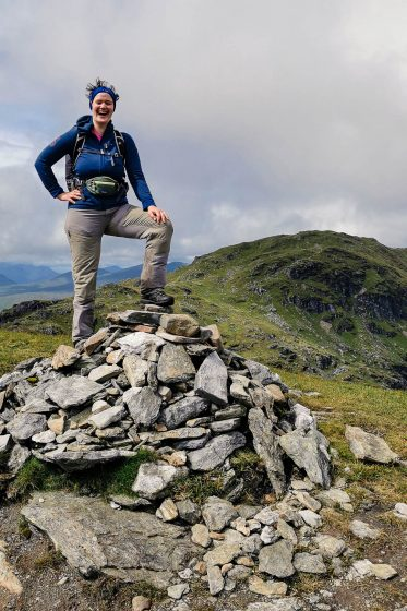 A woman standing triumphant on top of a summit cairn in Scotland