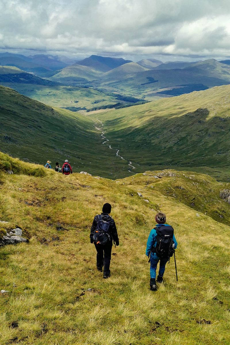 women walking down a grassy path in a Scottish glen