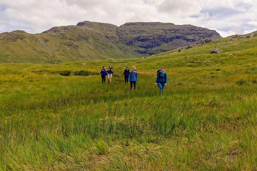 Women walking through high grass below mountains in Scotland
