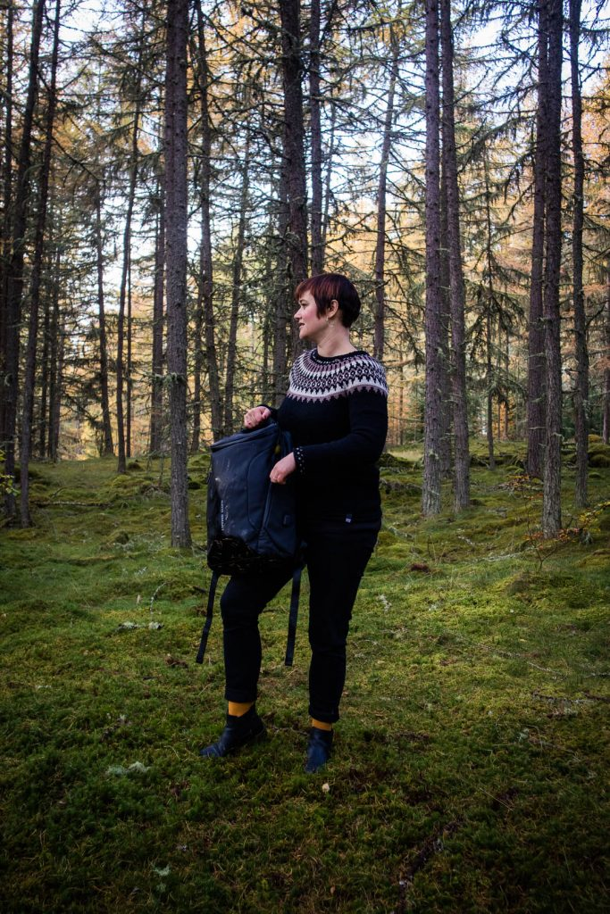 Woman standing in the forest and holding a backpack