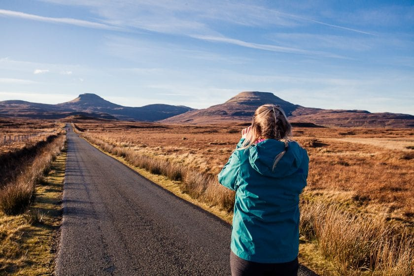 Woman standing on a road on the Isle of Skye.