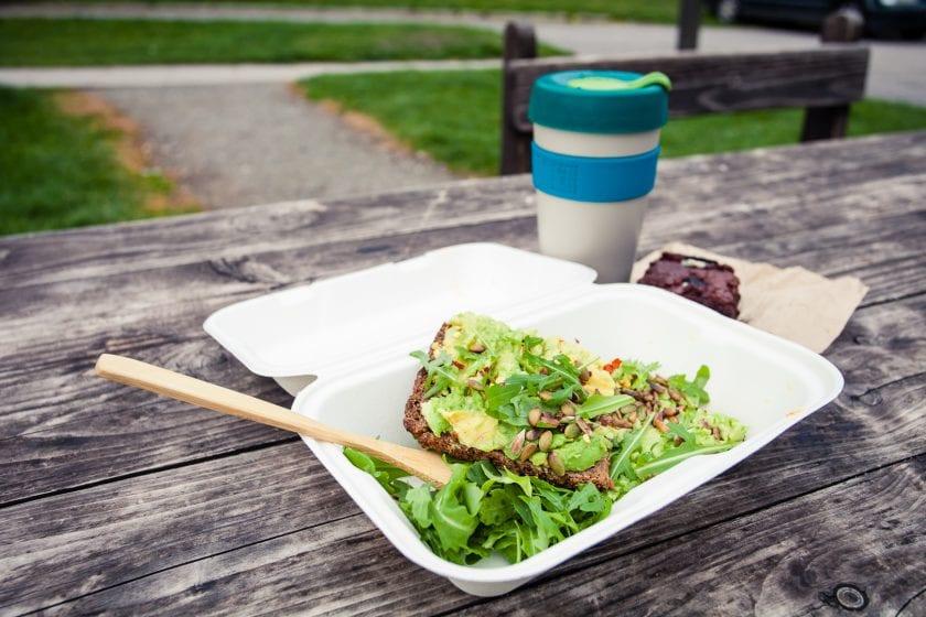 Open avocado sandwich in a takeaway box.