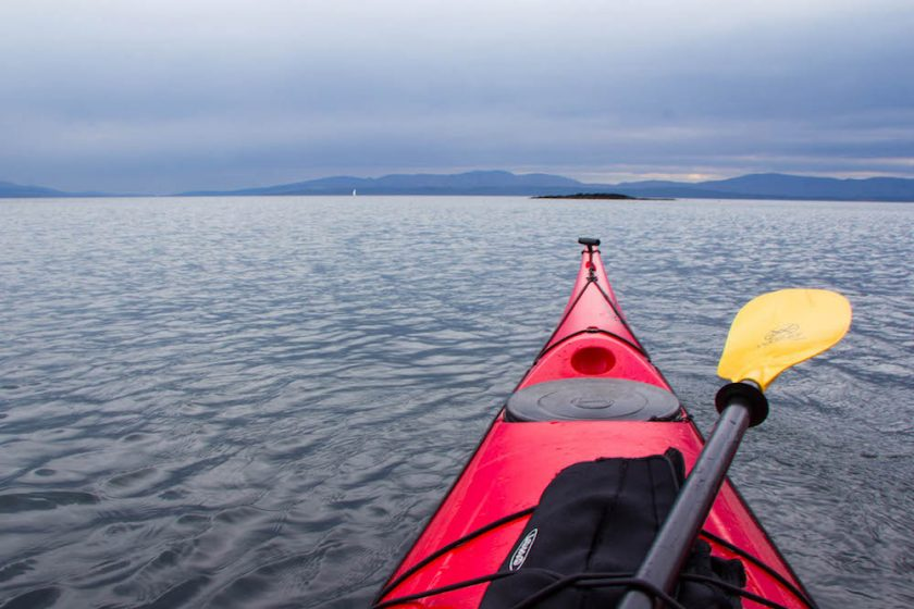 tip of a sea kayak on the water and islands in the background with moody sky