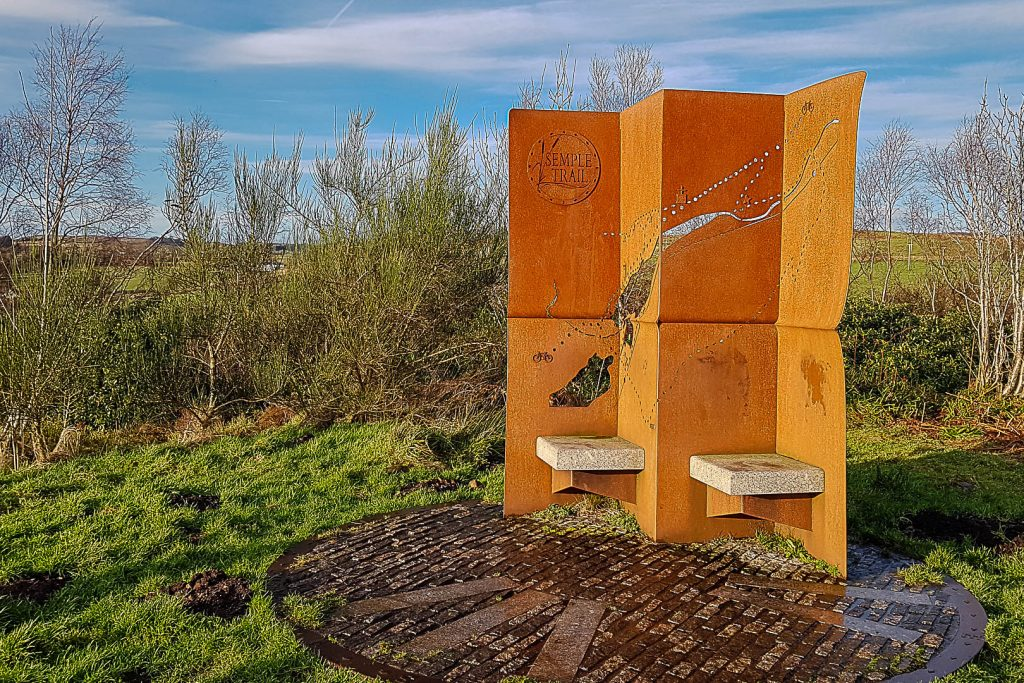 A rust-coloured wind shelter with seats on the Semple Trail at Lochwinnoch near Glasgow
