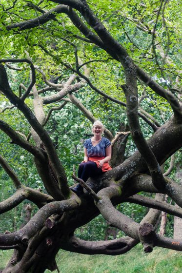 A woman climbing trees at Seven Lochs Wetland Park, Glasgow, Scotland